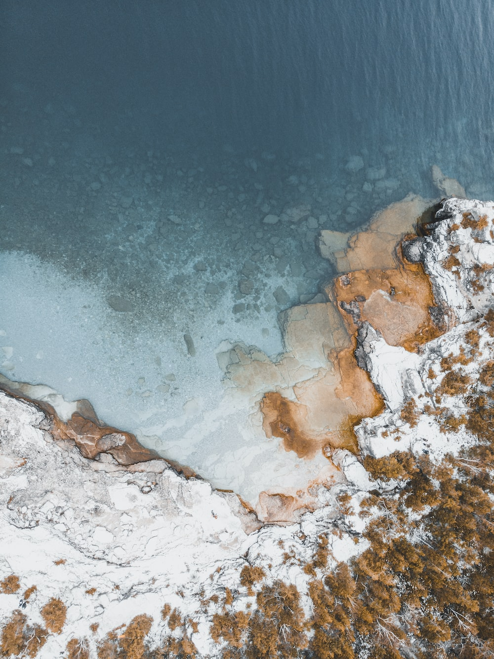 aerial photography of snow-covered cliff near body of water during daytime
