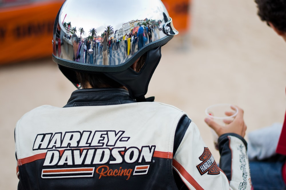 person wearing white and blue Harley-Davidson jacket