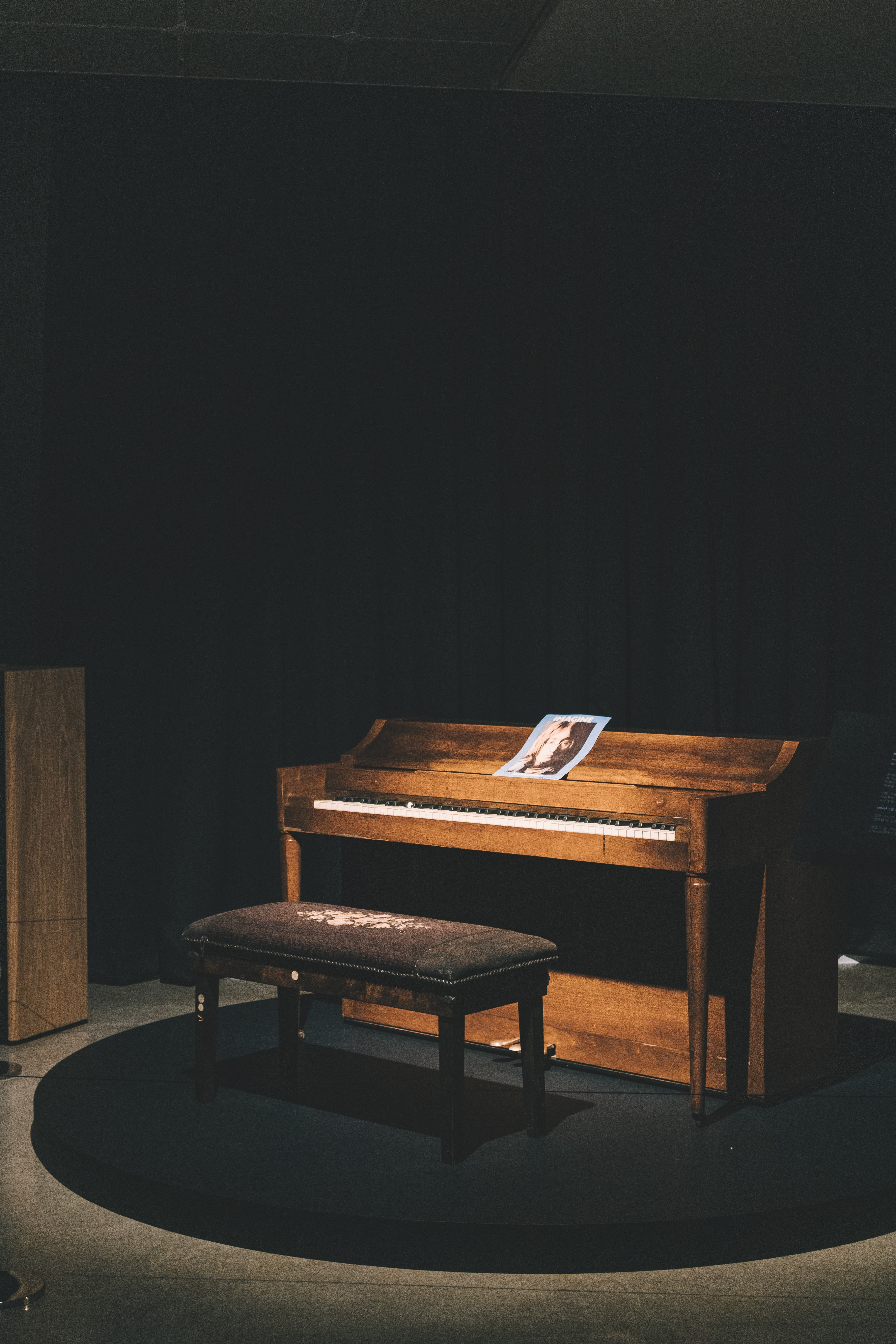 brown wooden upright piano with ottoman bench and light turned-on