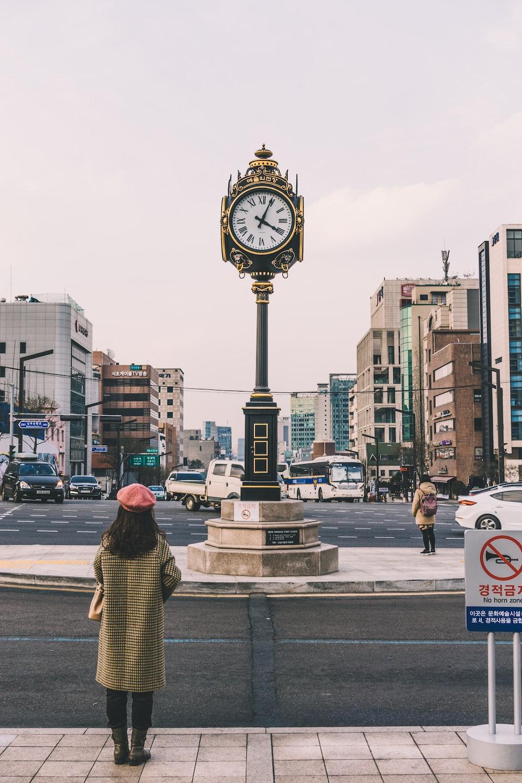 woman standing on street facing clock