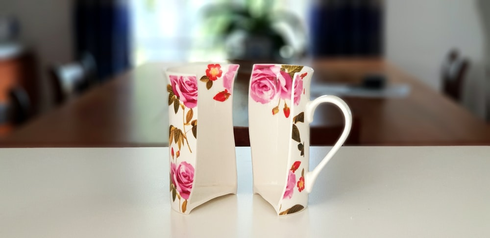 pink and white floral half ceramic mug on top of table