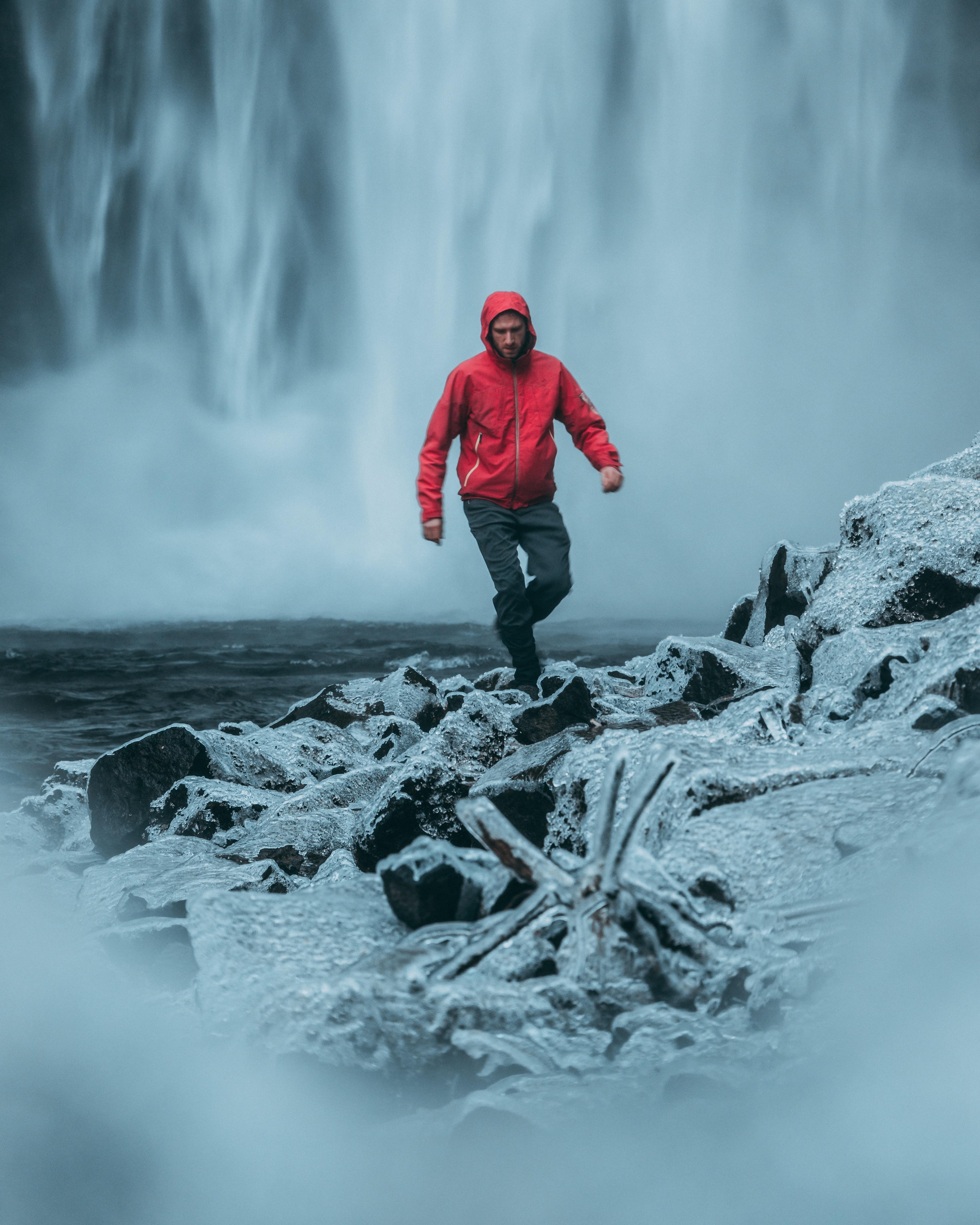 man walking near water falls during daytime