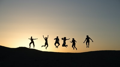 six silhouette of people jumping during sunrise silhouette teams background