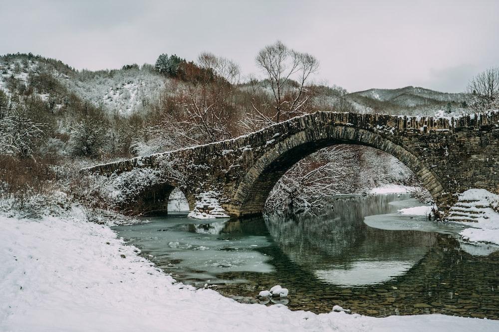 snow covered grey brick bridge during winter