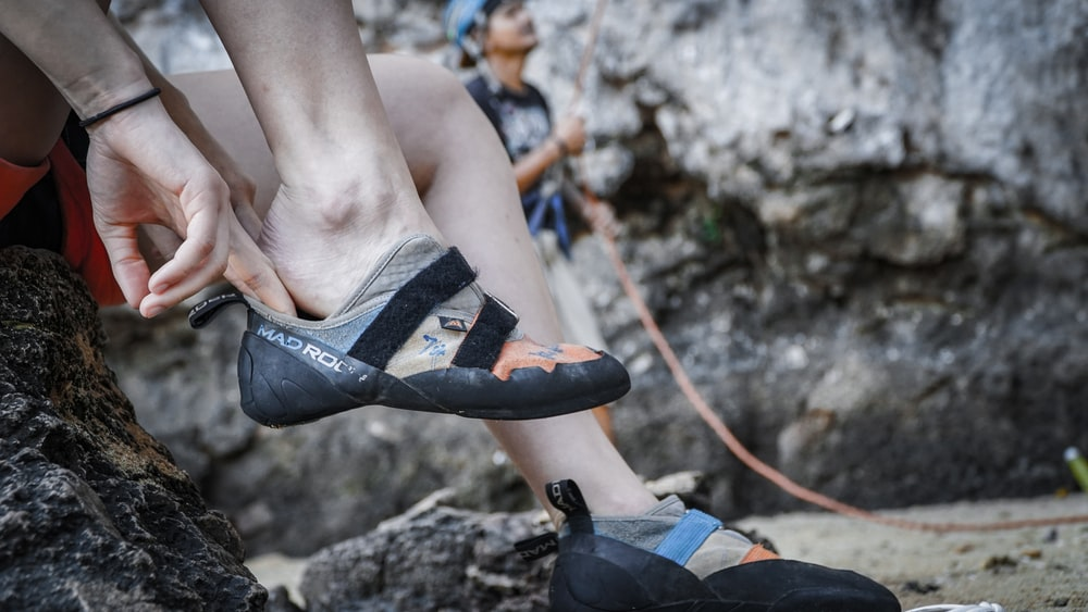 close-up photography of person wearing hiking shoes