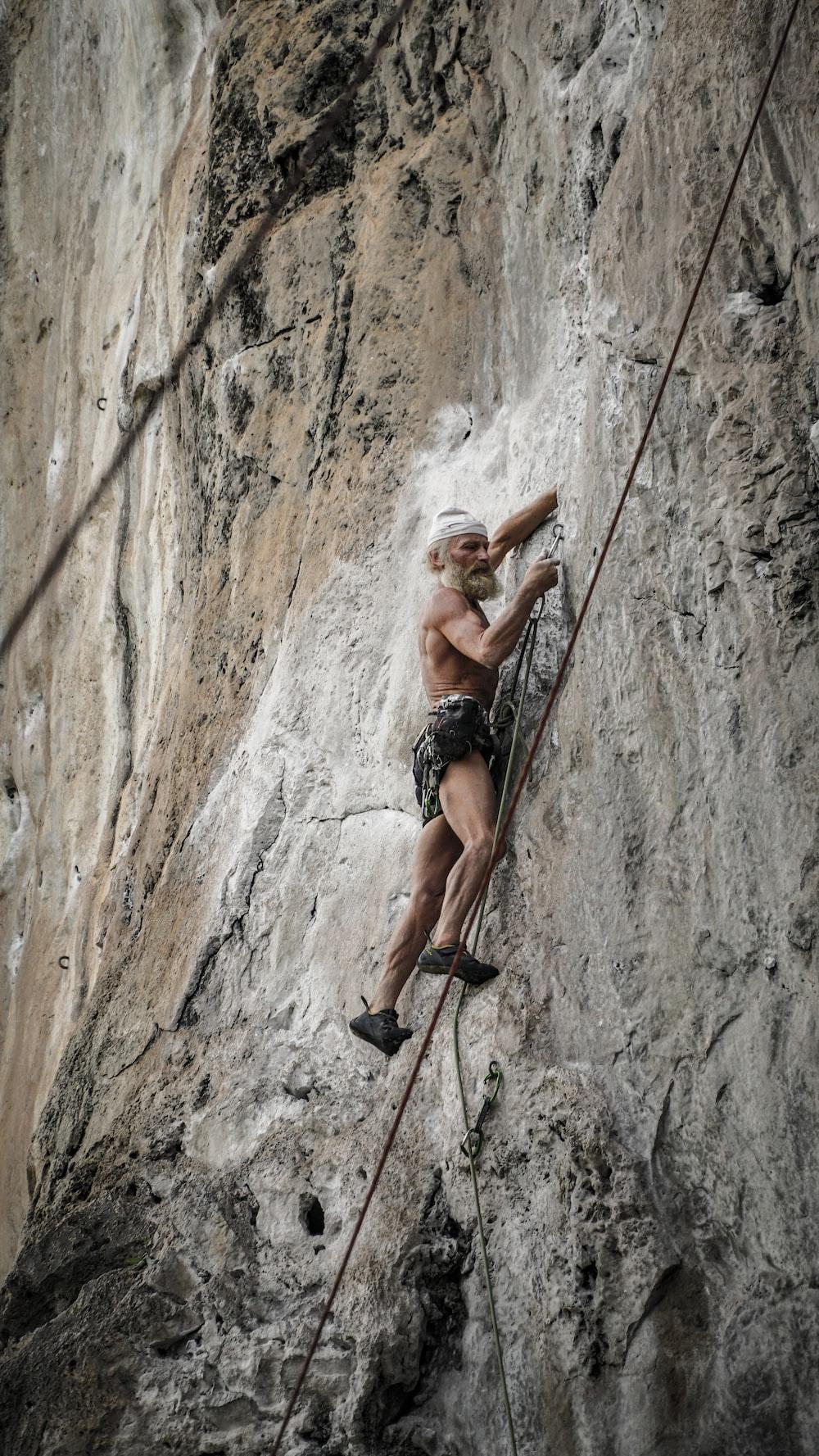 man climbing hill during daytime