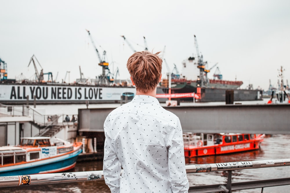man in white dress shirt standing on near harbor