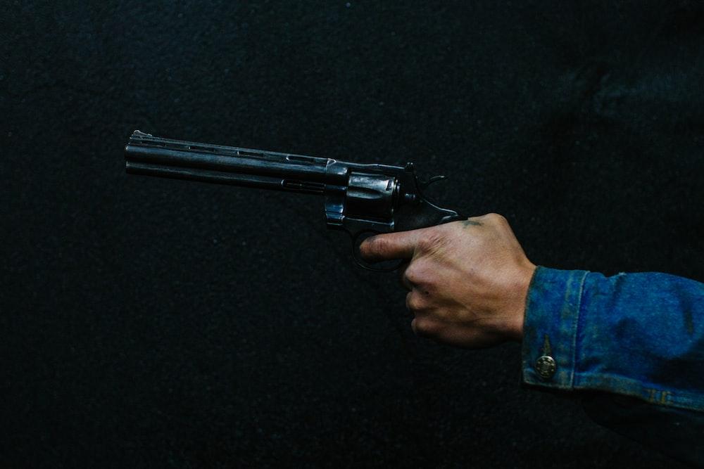 person holding revolver