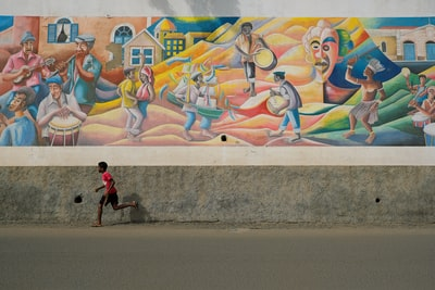 boy running beside multicolored wall painting during daytime cabo verde zoom background