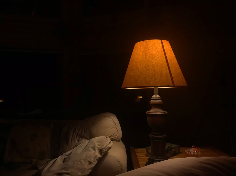 brown table lamp beside sofa turned on