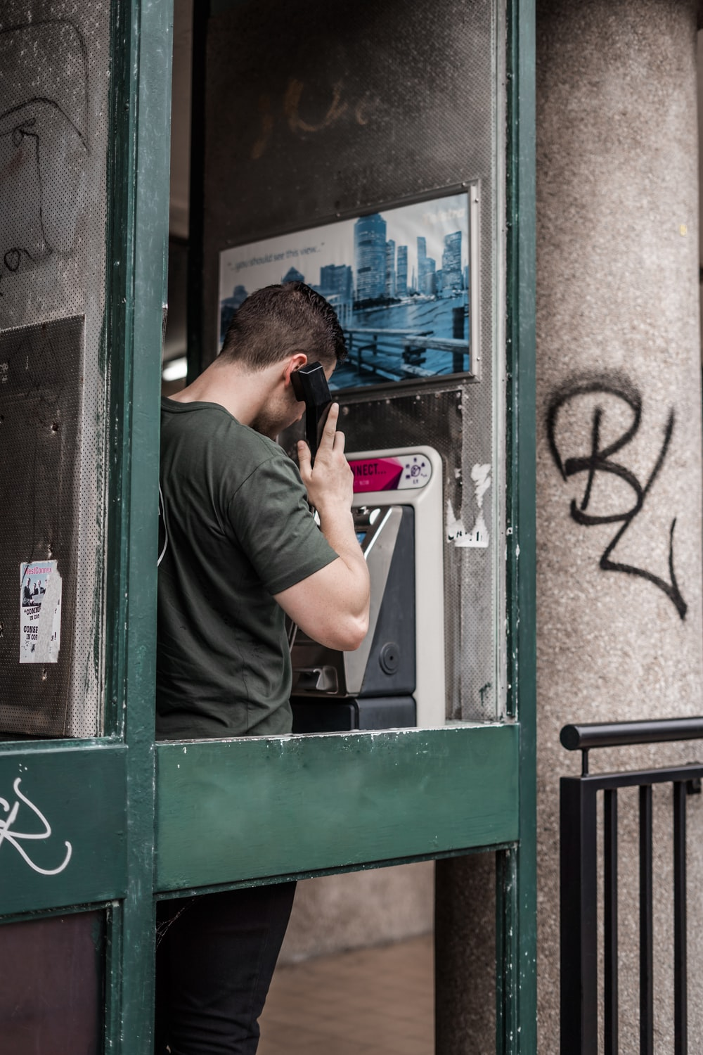 man standing while using telephone