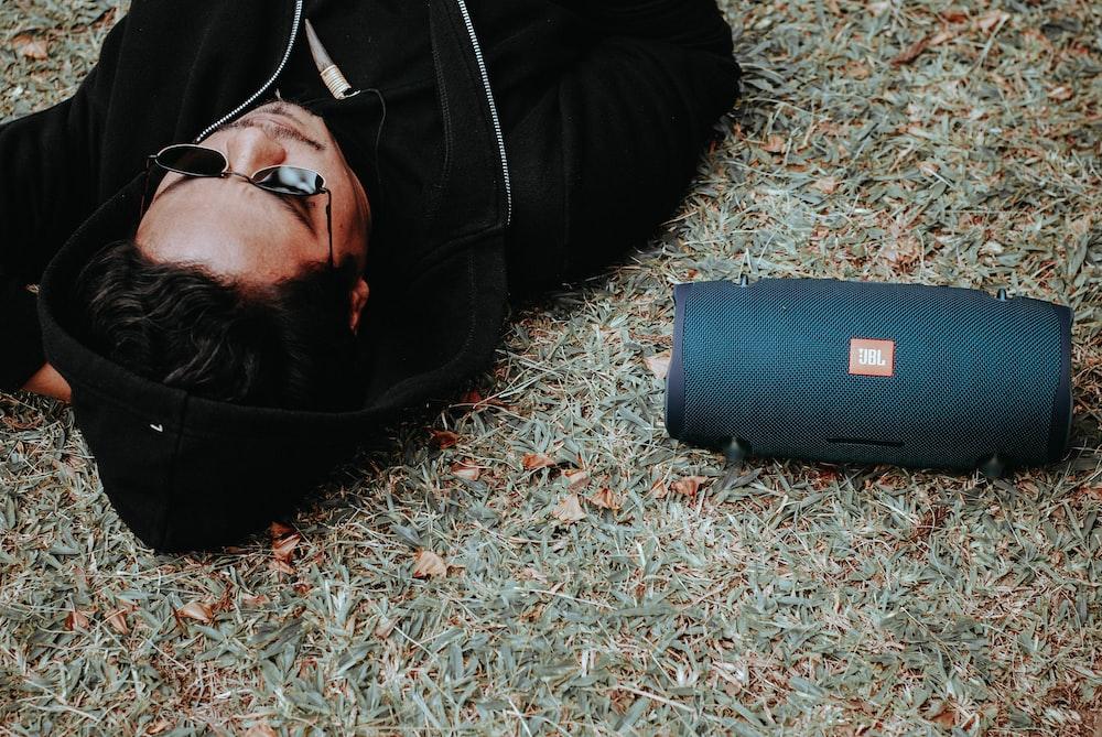 man lying on grass beside black JBL Bluetooth speaker