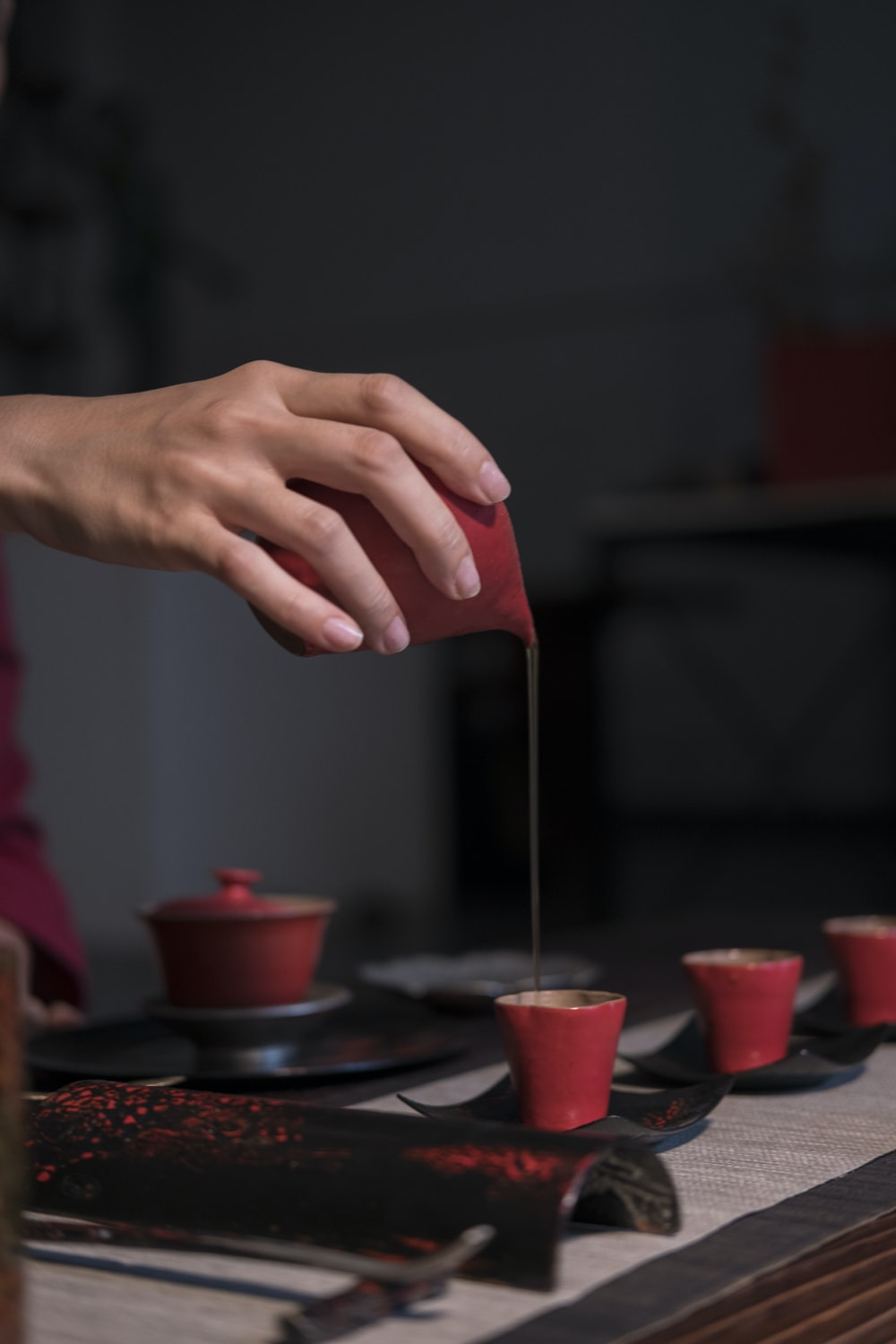 person pouring brown liquid on red cup