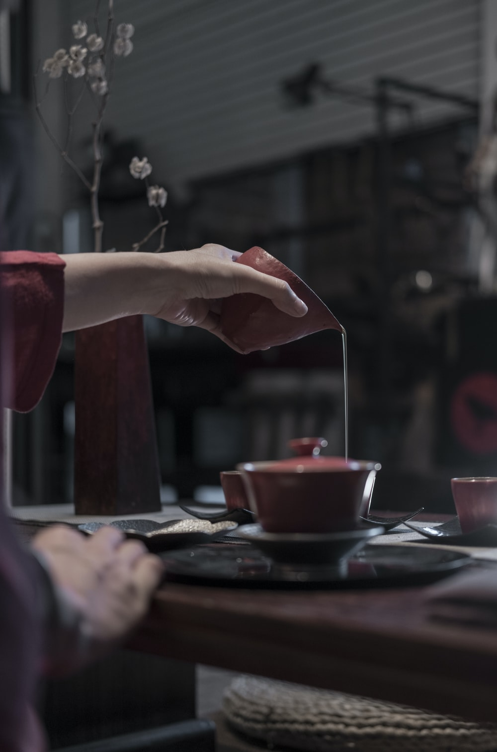 person pouring liquid on cup