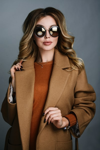 woman wearing brown long coat and round sunglasses