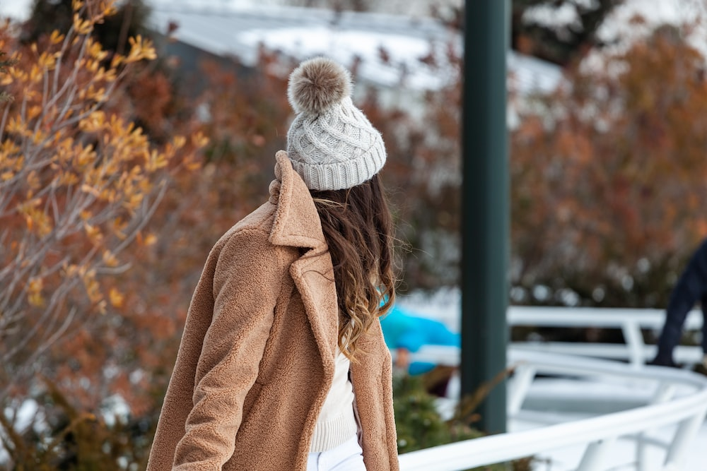 woman wearing bobble hat and looking behind