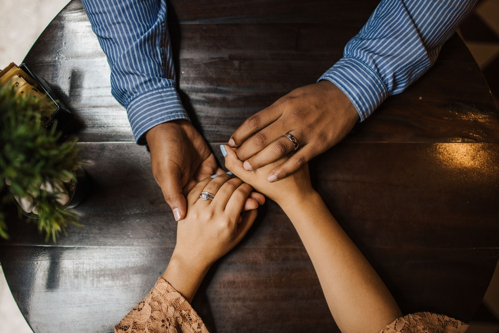 hands holding on brown wooden table