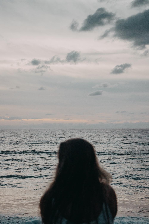 woman wearing white top standing near ocean