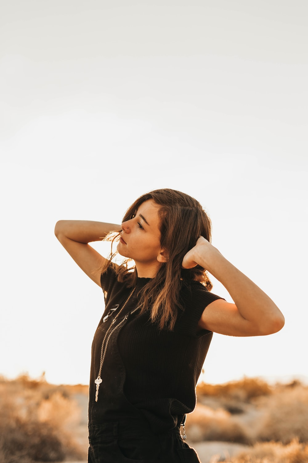 standing woman with two hands on head during daytime