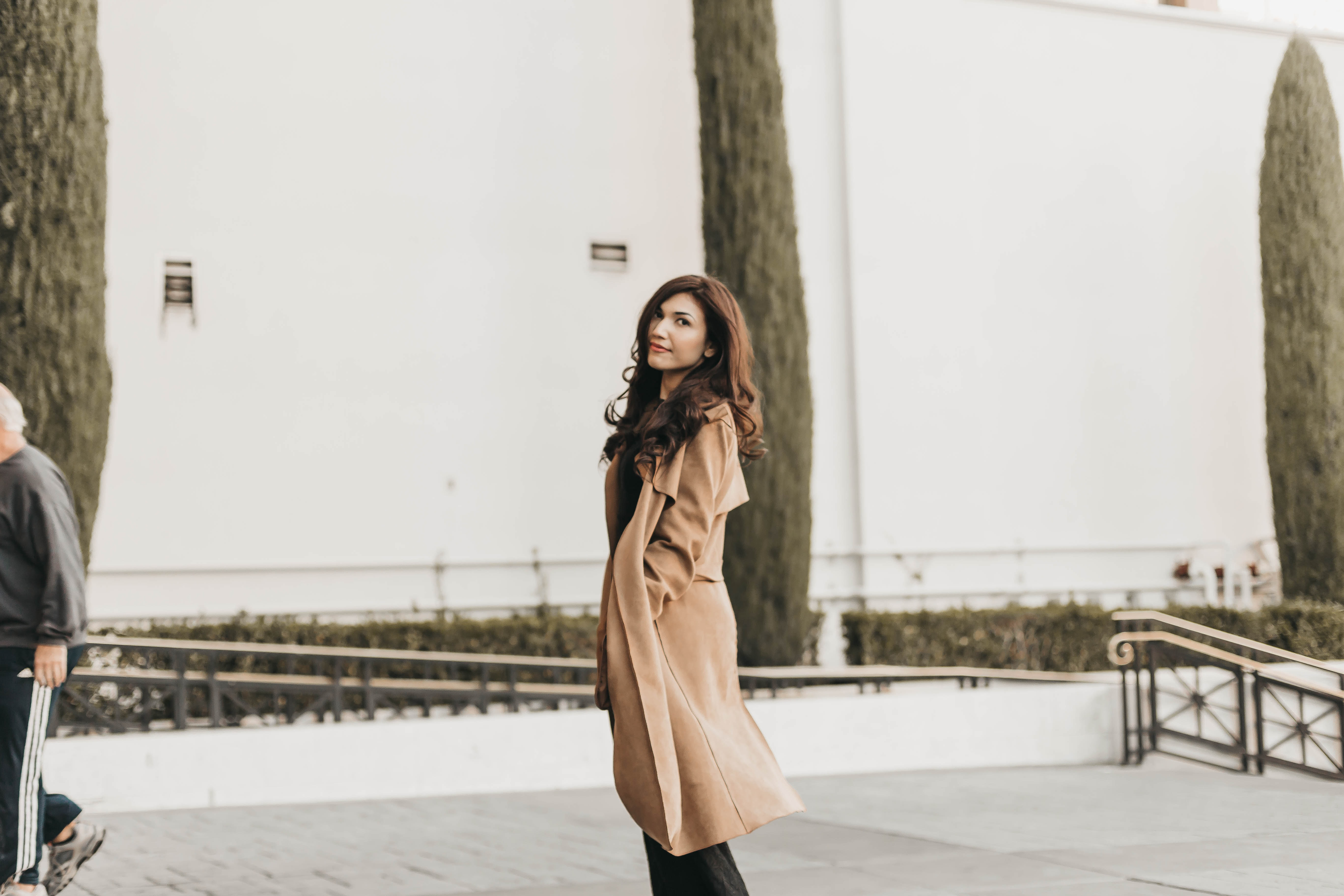woman standing wearing brown trench coat during daytime