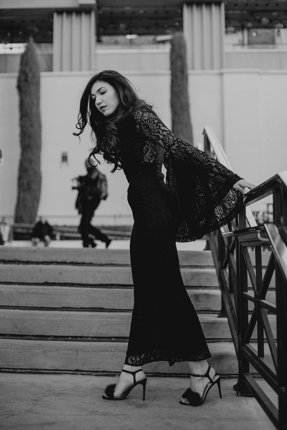 grayscale photography of woman wearing dress standing beside railing