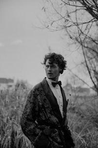 grayscale photography of man wearing tuxedo