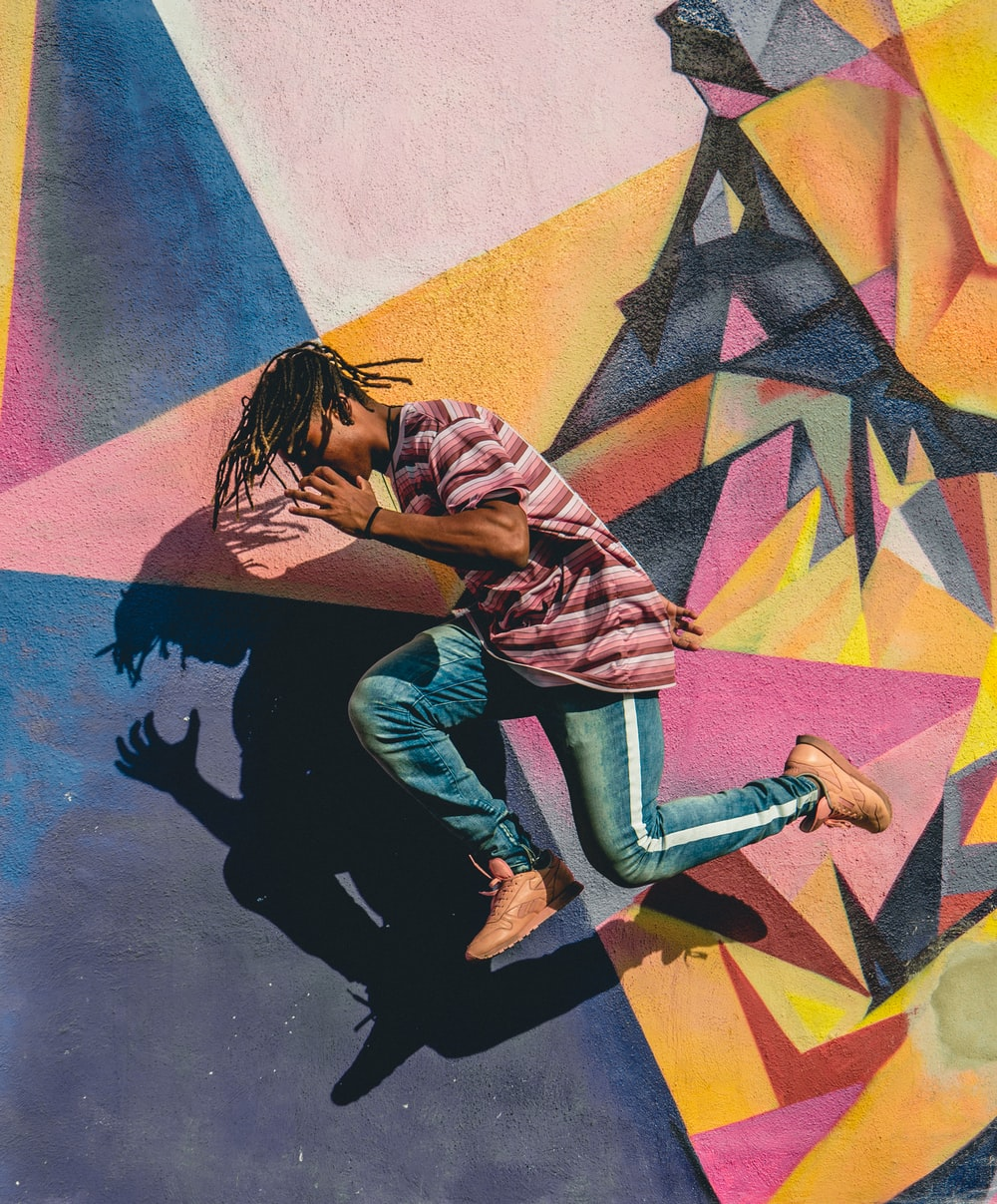 man jumping beside multicolored wall