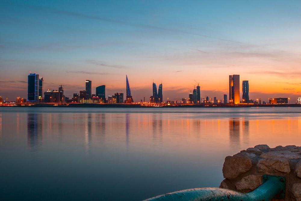city buildings beside body of water under blue sky