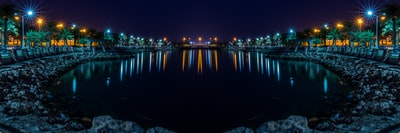 calm water front of street lights at night bahrain zoom background