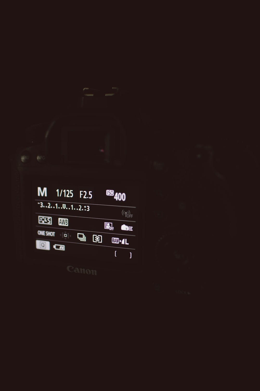 turned-on black Canon DSLR camera