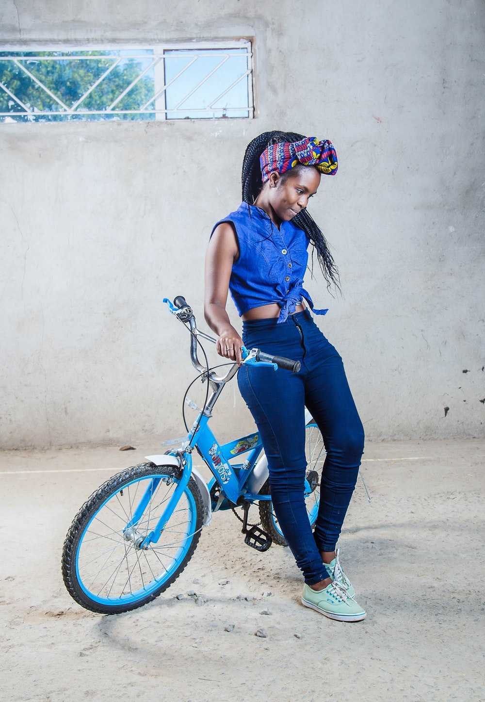 woman sitting on blue bicycle