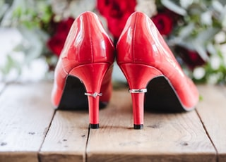 pair of red patent leather heels on wooden surface