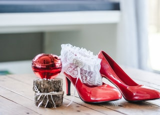 pair of red leather heels on wooden table