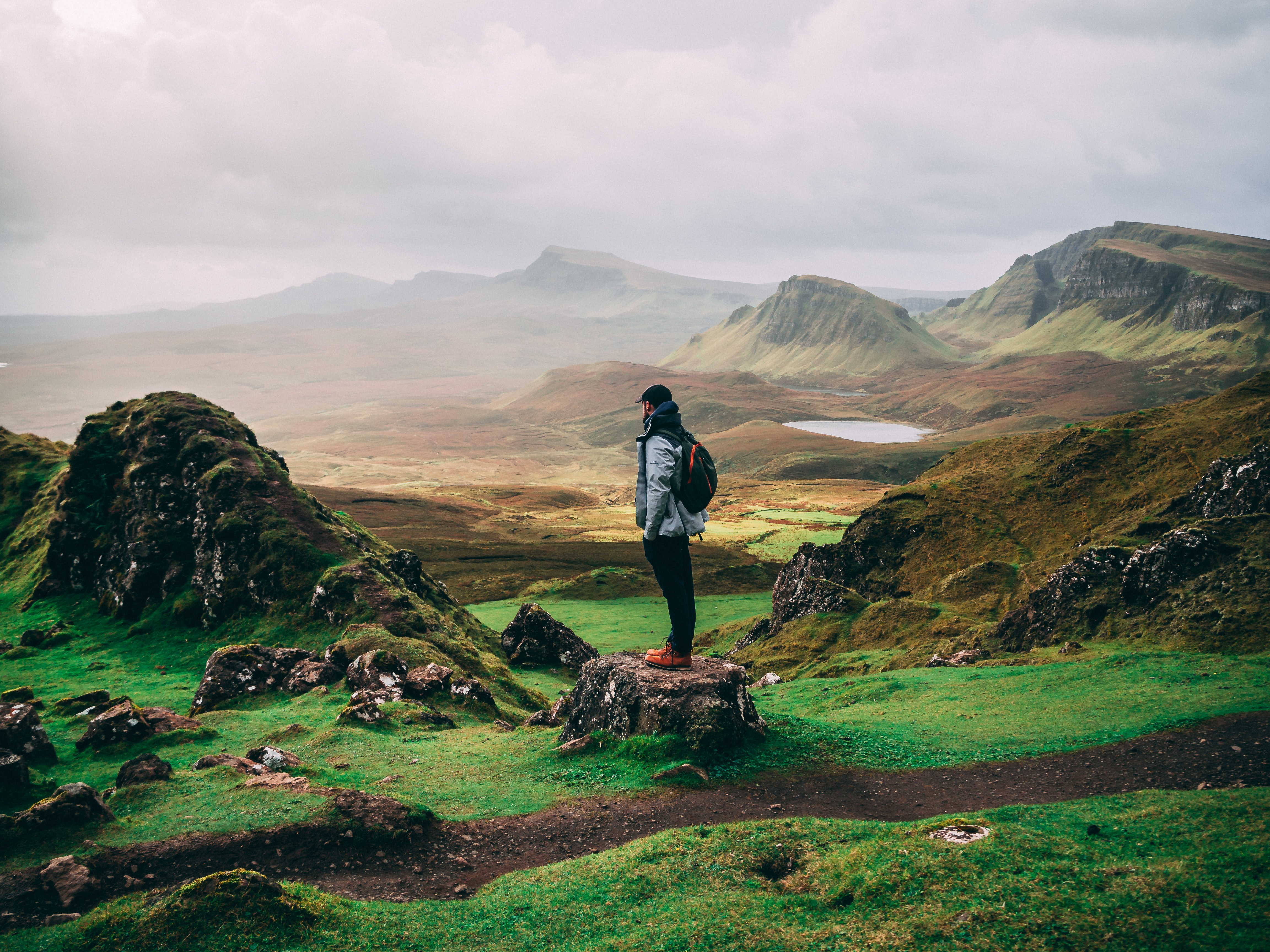 standing woman with backpack facing mountains