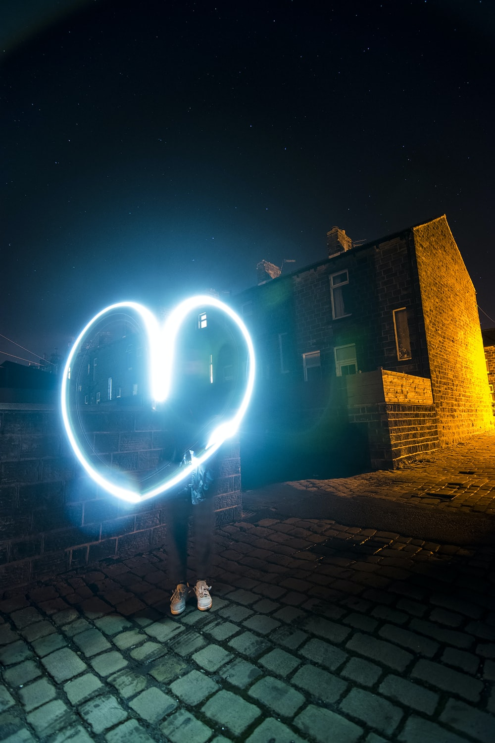 person holding heart wool fire beside building during nighttime