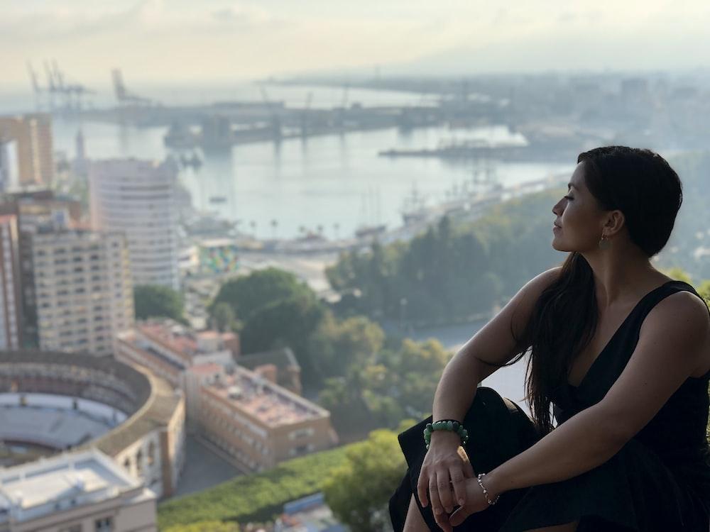 sitting woman facing buildings on selective focus photograph