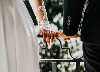 couple holding black metal bar during daytime