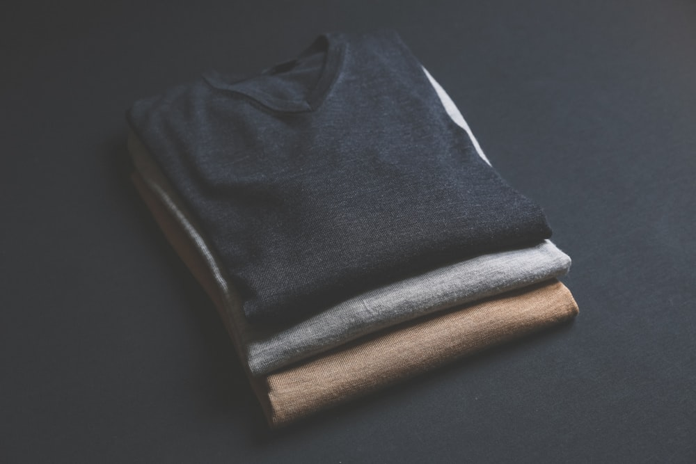 three black,grey,and brown V-neck shirt on black surface