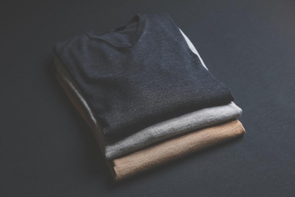 three black,grey,and brown V-neck shirt on black surface