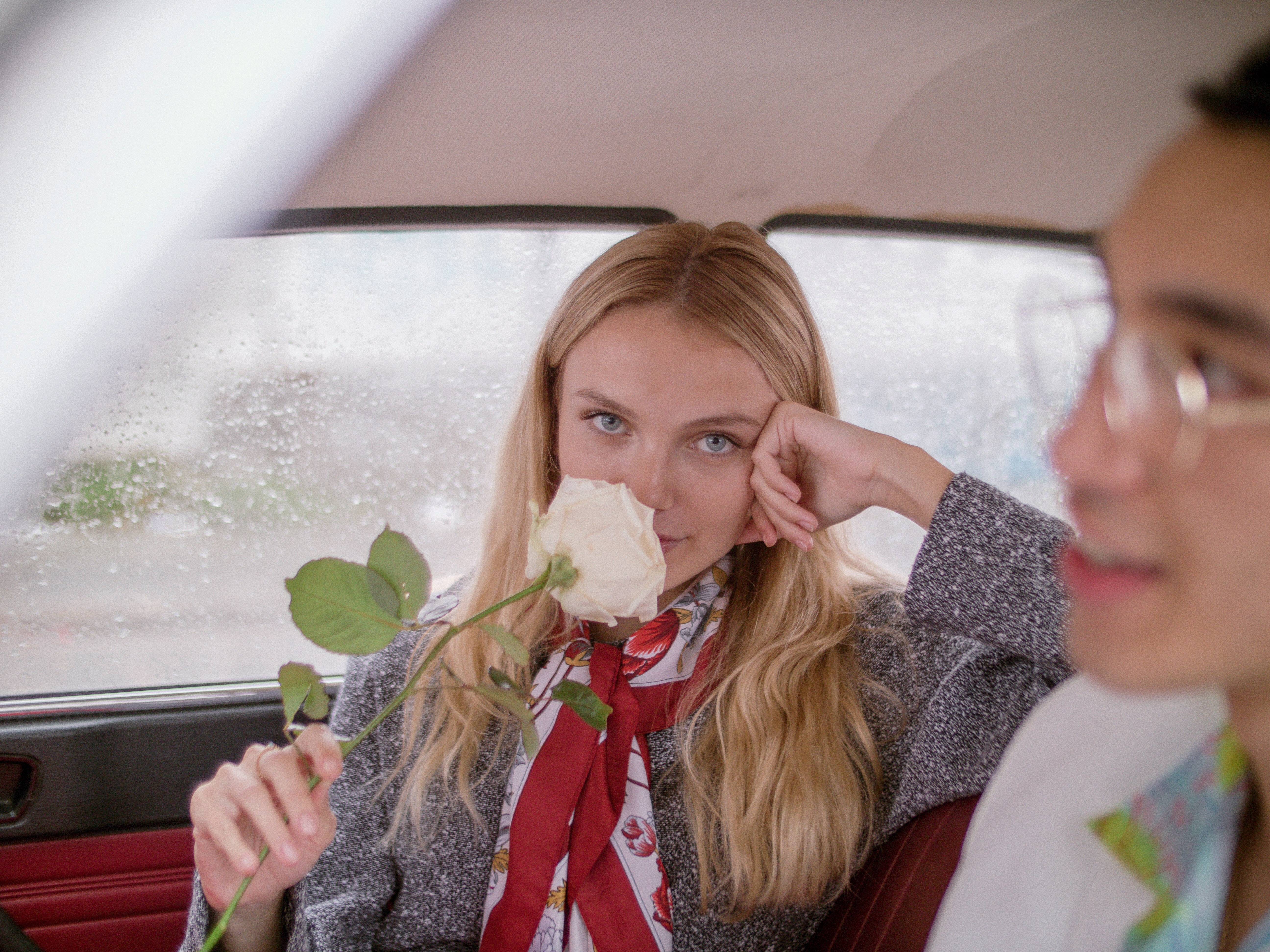 woman smelling the flower while sitting on car seat inside vehicle