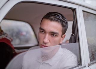 man sitting inside vehicle during daytime
