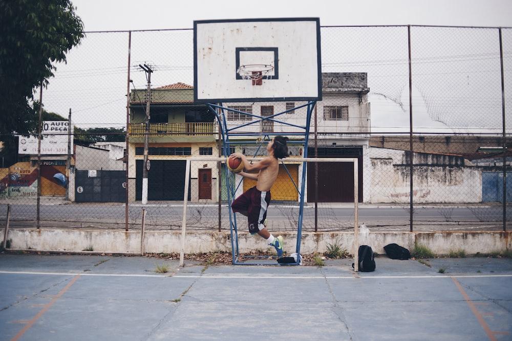 man wearing brown shorts doing lay-up near basketball ring during daytime