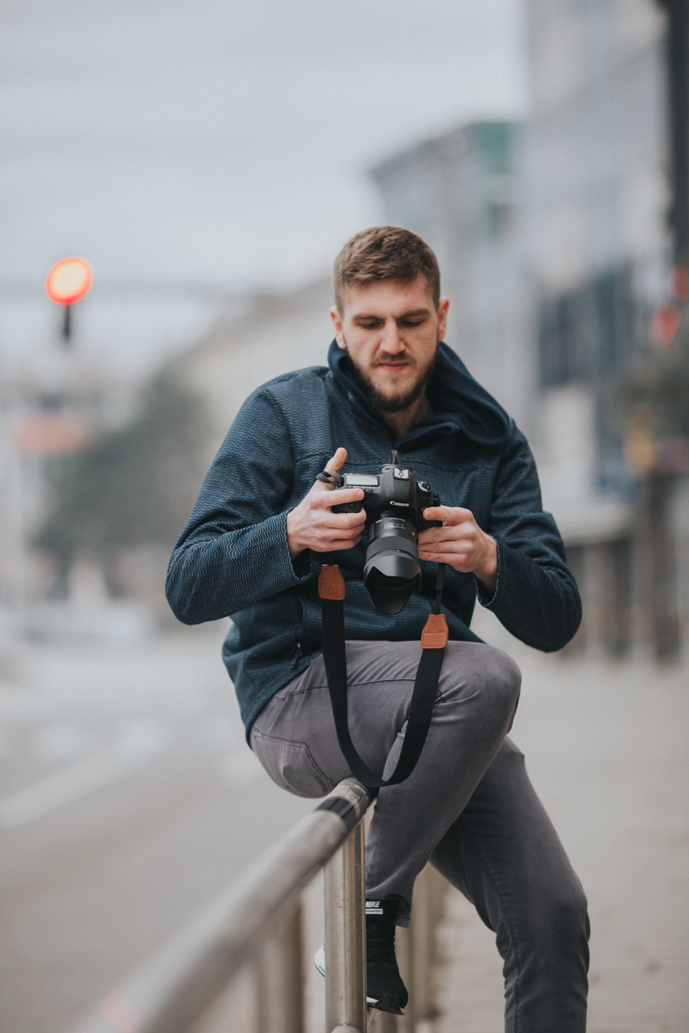 man sitting on gray railing while holding DSLR camera during daytime