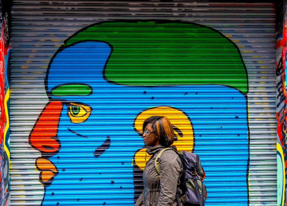 woman wearing grey jacket walking near blue, orange, and green face wall painting
