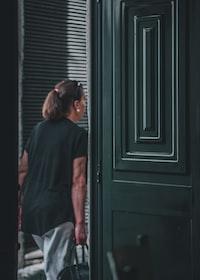 man carrying black handbag while walking