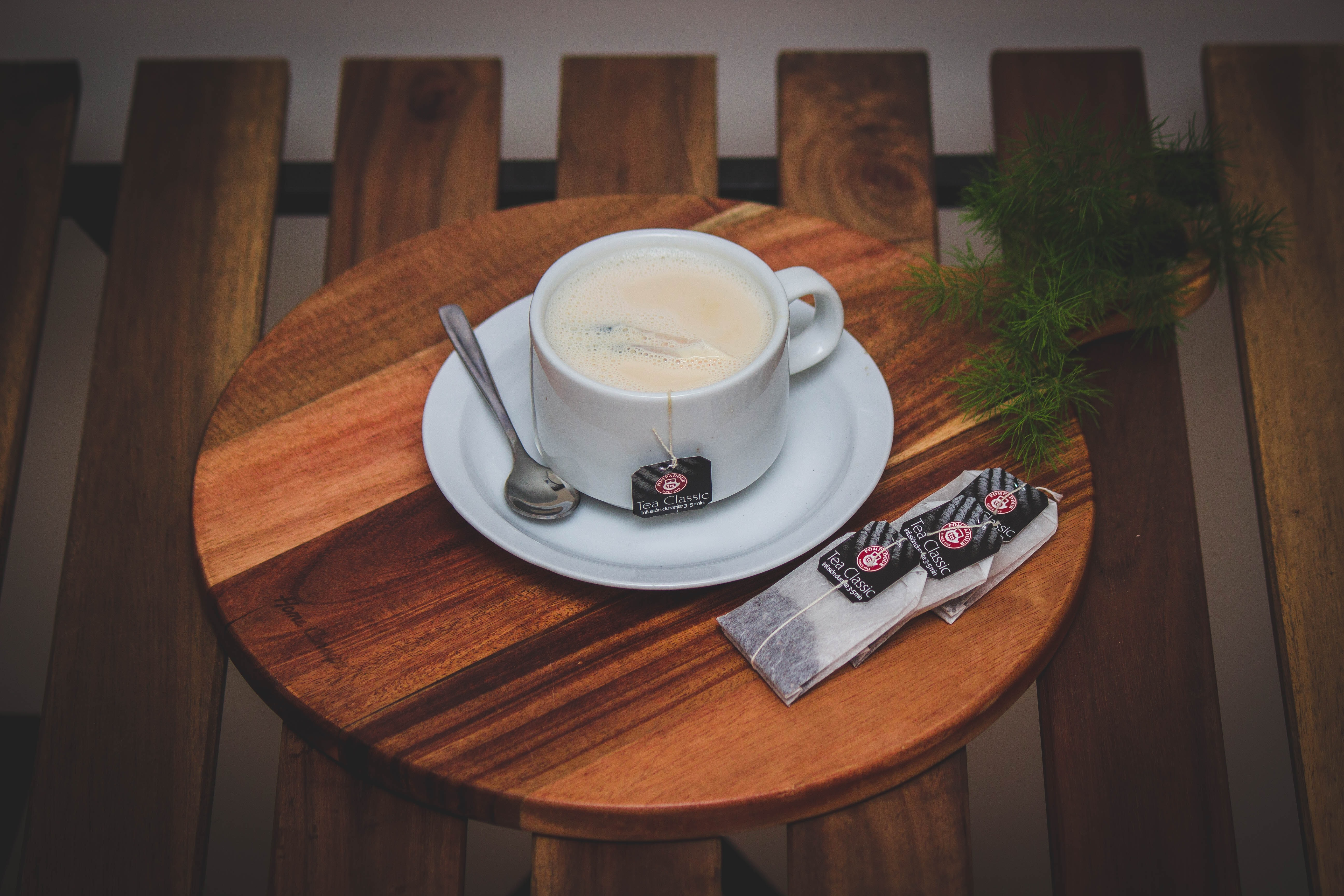 white teacup on top of white saucer on brown wooden tray