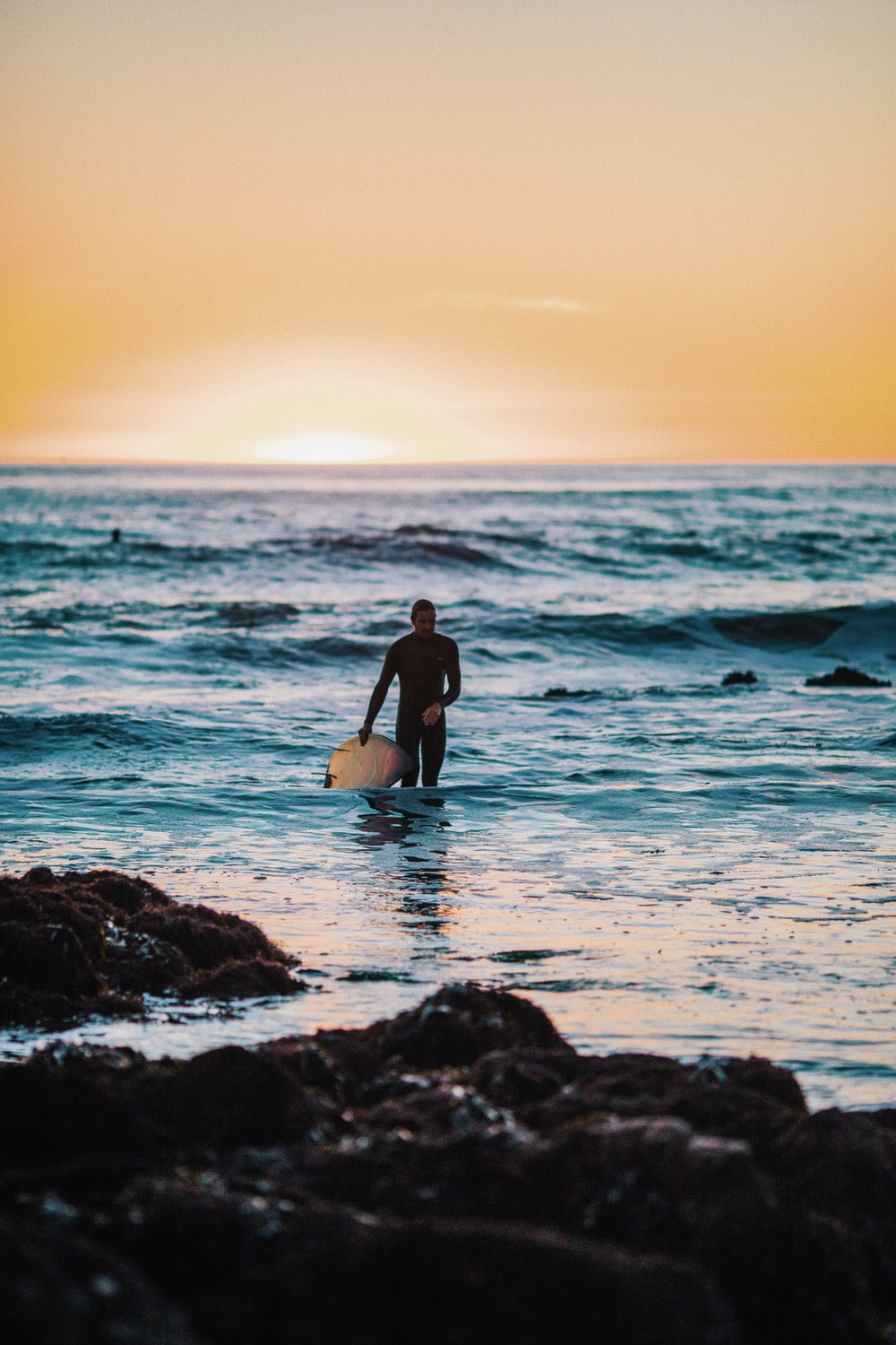 man holding surfboard at beach during daytime