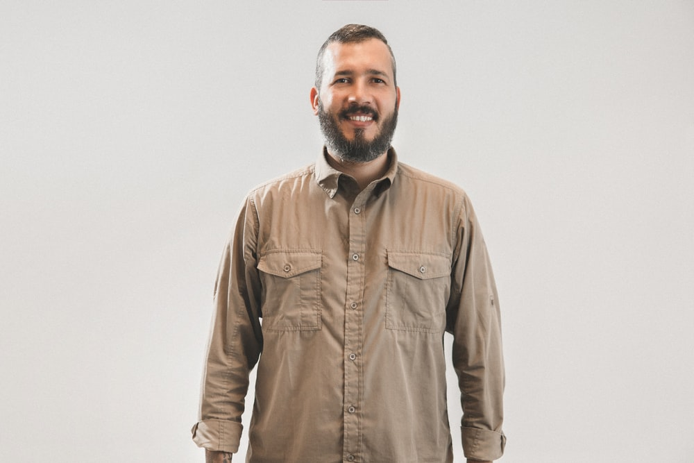 smiling man in brown dress shirt on focus photography