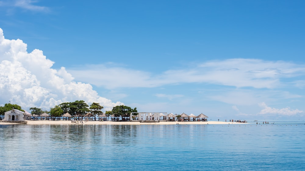 green trees and huts on white sand island surrounded by sea water during daytime