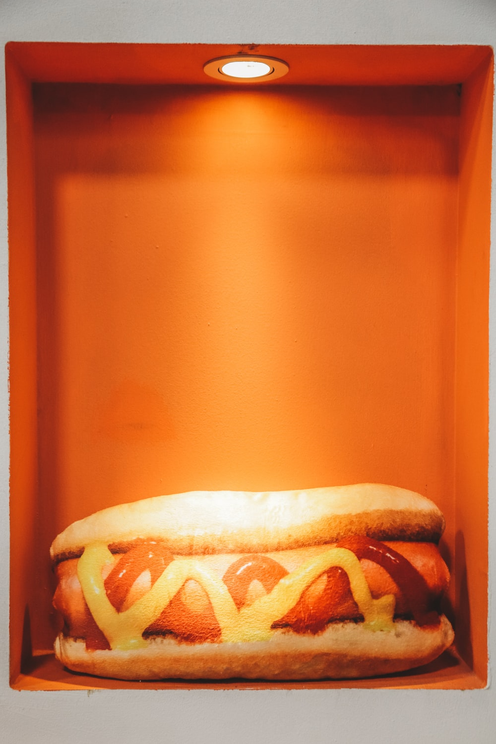 hotdog in bun with ketchup and mustard inside lighted box